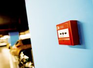 Fire alarm button on blue wall.